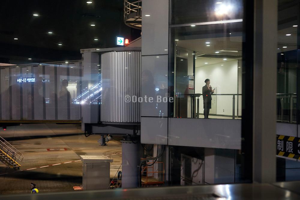 stewardess waiting at the boarding gate during night Narita airport Tokyo Japan
