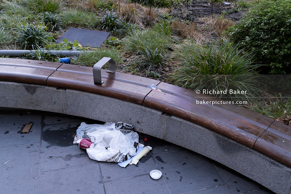 Litter gathers beneath a bench in the plaza of a quiet Leadenhall where lunchtime workers usually gather and which is habitualy swept and cleaned by contractors, during the third lockdown of the Coronavirus pandemic, in the 'City of London', the capital's financial district, aka The Square Mile, on 2nd February 2021, in London, England.