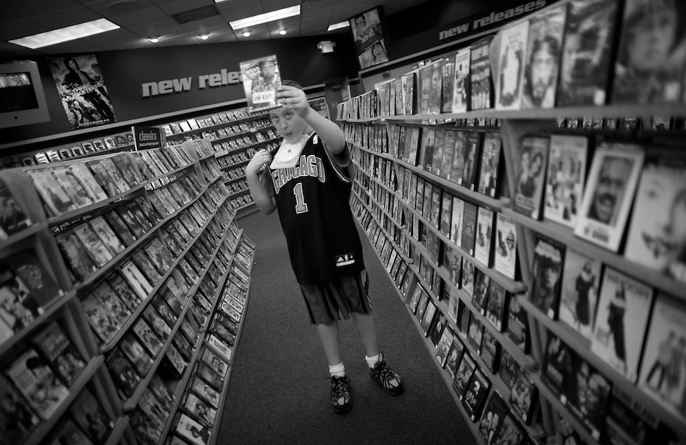 Parker Roos, who suffers from Fragile X, holds up a video as he asks his mother Holly for permission to rent it at a video store in Canton, Illinois, April 4, 2012. .  REUTERS/Jim Young