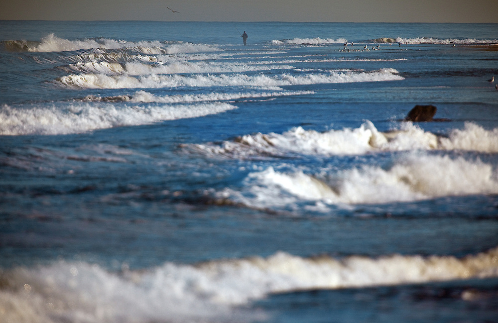 A fisherman in the distance working the shoreline at Sandy Hook NJ one day after a powerful coastal storm (nor'easter) pumulled the coastline.
