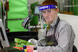 © Licensed to London News Pictures. 15/04/2020. London, UK. Waitrose employee Fergall (16) wears a face shield while on the shop floor. Staff at Waitrose at Westfield White City are now issued with PPE (personal protection equipment) before starting shift which they are encouraged but not obliged to wear when coming into contact with high volumes of shoppers. The face shields protect the wearer from aerosol ejection, one of the key vectors associated with the transmission of the coronavirus COVID-19. While frontline workers in other sectors notably in healthcare - NHS and care homes - are struggling to access appropriate protection some supermarkets have taken matters into their own hands providing their own PPE and cleaning protocols. Photo credit: Guilhem Baker/LNP
