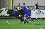 AFC Wimbledon defender Chris Robertson (34) chased own Bury FC striker Hallam Hope (24) during the The Emirates FA Cup 1st Round Replay match between AFC Wimbledon and Bury at the Cherry Red Records Stadium, Kingston, England on 15 November 2016. Photo by Stuart Butcher.