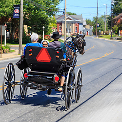Intercourse, PA - June 12, 2016: Old Order Amish use a horse drawn open buggy as their primary transportation in rural Lancaster County, Pennsylvania.8