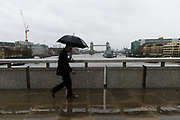 A man with a black umbrella walking across London Bridge in London, England during rain and wet weather in the capital on  December 01, 2018