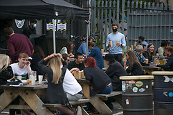 © Licensed to London News Pictures. 04/07/2020. London, UK. People enjoy drinks in Hackney Wick, east London, as pubs reopen following the easing of coronavirus lockdown restrictions across England. The easing of restrictions, which were imposed on March 23, allows businesses including pubs restaurants and hair salons, to reopen to members of the public with measures in place to prevent the spread of the coronavirus.  Photo credit: Marcin Nowak/LNP