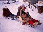 Inupiat children Sophia Ahmaogak, Lorraine Tagarook and Krystle Ahmaogak playing with sleds, Ahmaogak home, Wainwright, Arctic Coast of Alaska.