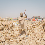 Afghan worker, refugee, breaking stones that will be used for road construction.