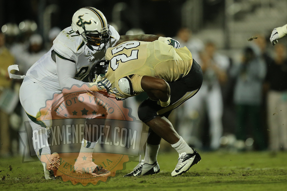South Florida Bulls defensive end Ryne Giddins (97) tackles UCF Knights running back William Stanback (28) during an NCAA football game between the South Florida Bulls and the 17th ranked University of Central Florida Knights at Bright House Networks Stadium on Friday, November 29, 2013 in Orlando, Florida. (AP Photo/Alex Menendez)