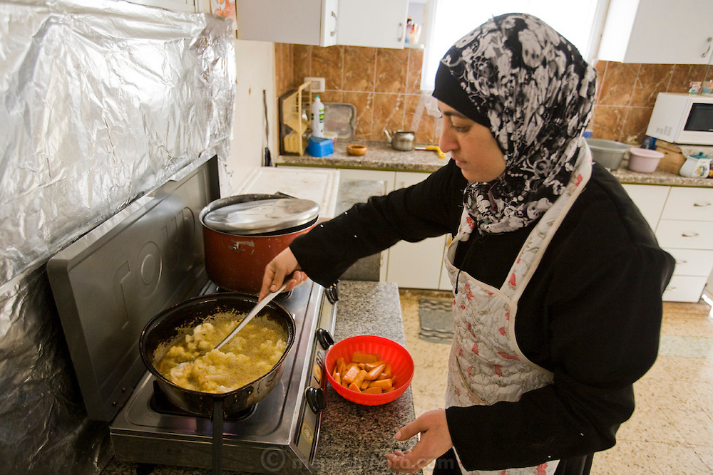 Abdul-Baset Razem's wife, Munira, tends to the makloubeh at the stove at their extended family home in the village of Abu Dis, East Jerusalem.  (Abdul-Baset Razem is featured in the book What I Eat: Around the World in 80 Diets.) MODEL RELEASED.