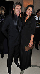ROGER TAYLOR and his wife GISELLA at the Harper's Bazaar Women of the Year Awards 2011 held at Claridge's, Brook Street, London on 7th November 2011.