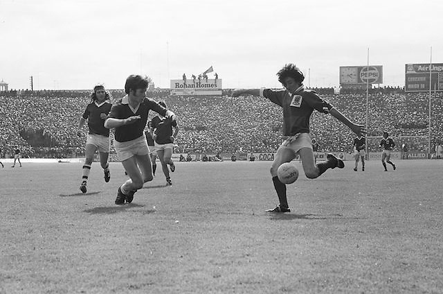 Galway kicks the ball as Dublin dives in an attempt to block him during the All Ireland Senior Gaelic Football Championship Final Dublin V Galway at Croke Park on the 22nd September 1974. Dublin 0-14 Galway 1-06.