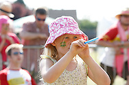Photo by Andrew Tobin/Tobinators Ltd - 07710 761829 - Madeline Bresler takes aim on her way to winning the Junior World Championship during the World Peashooting Championships held at Witcham, Cambridgeshire, UK on 13th July 2013. Run in conjunction with the village fair, the Championships have been held in Witcham since 1971 when they were started by a Mr Tyson, the village schoolmaster, in order to raise funds for the village hall.Competitors come from as far afield as the USA and New Zealand to attempt to win the event. The latest technology is often used, including laser sights and titanium and carbon fibre peashooters. All peashooters must conform to strict length rules, not exceeding 12 inches, and have to hit a target 12 feet away. Shooting 5 peas at a plasticine target attached to a hay bale, the highest scorers move through the initial rounds to a knockout competition, followed by a sudden death 10-pea shootout.