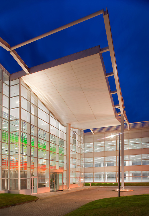 Large exterior office entrance reception at night with dark blue sky and lights on