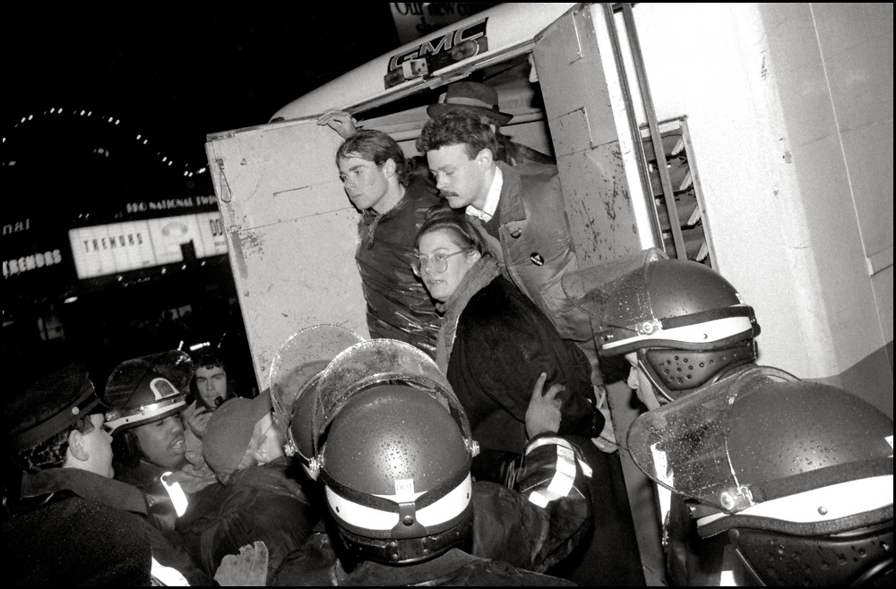 In January of 1990, Karin Timour, of ACT UP, was arrested at an action protesting the selection of Dr. Woodrow Myers for NYC Commissioner of Health, by Mayor David Dinkins. When Myers was the Indiana State Health Commissioner he had attempted to implement mandatory HIV testing, partner tracing and quarantine.
