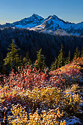 Snow-dusted fall color lines a ridge overlooking several mountains in the Tatoosh Range in Mount Rainier National Park, Washington. Unicorn Peak, with an elevation of 6,971 feet (2,125 meters), is the highest peak in the Tatoosh Range and is visible on the right. West Unicorn Peak, with an elevation of 6,840 feet (2,080 meters), is the second-highest peak in the range and is in the center of the image, partially hidden behind Foss Peak, which is 6,522 feet (1,988 meters) tall. The Tatoosh Range is a sub-range of the Cascade Range.