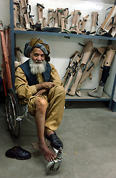 KABUL,AFGHANISTAN - SEPT. 11:  Mohammed Hazim who is crippled prepares to have braces made for him to enable him to walk at the ICRC hospital in Kabul, Afghanistan September 11,2002. (Photo by Ami Vitale/Getty Images)