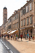 The main street Stradun Placa with traditional houses and flocks of tourists, view towards the city gate and Franciscan's church tower Dubrovnik, old city. Dalmatian Coast, Croatia, Europe.