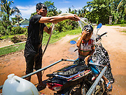02 JUNE 2016 - SIEM REAP, CAMBODIA: A man sprays water on his son after filling their water bottles at a public well west of Siem Reap. He said the well near his home had run dry so he was making 4 - 5 trips per day to the public well to get water for his home. Cambodia is in the second year of  a record shattering drought, brought on by climate change and the El Niño weather pattern. Farmers in the area say this is driest they have ever seen their fields. They said they are planting because they have no choice but if they rainy season doesn't come, or if it's like last year's very short rainy season they will lose their crops. Many of the wells in the area have run dry and people are being forced to buy water to meet their domestic needs.    PHOTO BY JACK KURTZ