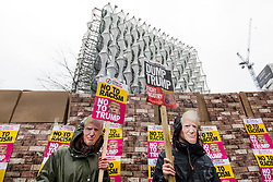 © Licensed to London News Pictures. 20/01/2018. London, UK. Two protesters wearing Donald Trump masks stand next to a model of the proposed border wall outside the new American Embassy in Nine Elms on the first anniversary of Trump's inauguration as US President. Trump has cancelled his planned February 2018 visit to the UK and has described the new embassy as a 'bad deal'. Photo credit: Rob Pinney/LNP