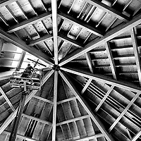 Workers on a lift squeeze a historic metal cross through a hole in  roof during construction of a new sanctuary at Resurrection Church in Aptos, California.<br /> Photo by Shmuel Thaler <br /> shmuel_thaler@yahoo.com www.shmuelthaler.com