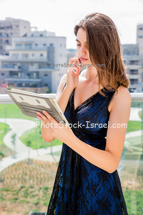 Young woman in formal dress uses atouchpad tablet while talking on a mobile phone on the balcony of her home