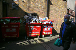 © Licensed to London News Pictures. 01/05/2020. London, UK. A man wearing a face covering walks past piles of rubbish collected in Wood Green, north London. The coronavirus lockdown continues to slow the spread of COVID-19 and reduce pressure on the NHS.  Photo credit: Dinendra Haria/LNP