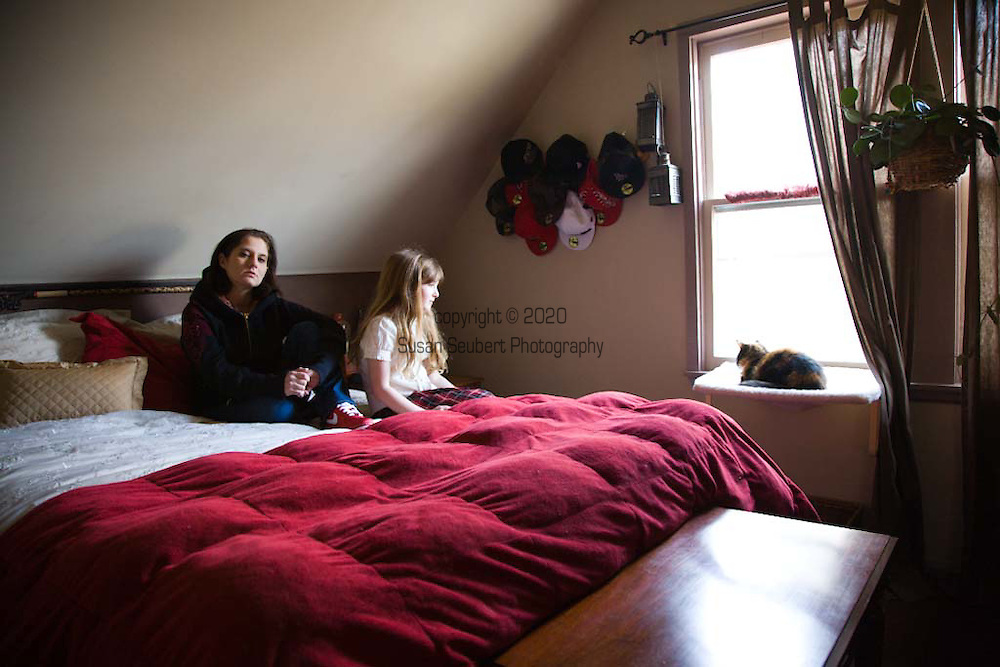 Author Margaret B. Jones with her daughter Rya Hickey in Margaret's bedroom in Eugene, Oregon.  On the wall behind her is her collection of hats. Their cat, Heathcliff, is sitting on his window perch.