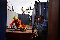 Chief Officer Elsayed Ahmed Mohamed, left, of Egypt, talks to A/B Seaman Fadi Joubili, of Lebanon, as he takes a break from tightening the lashings on the containers as they are loaded onto the vessel in Port Said, Egypt on April 9, 2008. The Bisanzio, a feeder ship taking containers from Port Said to Beirut, is Lebanese owned, has three different nationalities aboard, and flies a St. Vincent flag. The Suez Canal is one of the most important shipping routes in the world, as it allows allows two-way water transportation - most importantly between Europe and Asia without the circumnavigation of Africa.