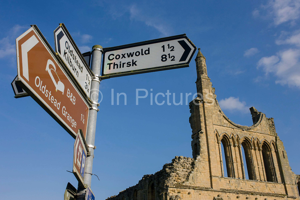Local signpost showing nearby village milage and the ruins of Cistercian Byland Abbey. Located near Coxwold and Oldstead and on the edge of the North Yorkshire Moors, Byland Abbey was described in the late 12th century as one of the shining lights of northern monasticism. The abbey rose to be one of the largest of the Savigniac order in Britain and the remains of the buildings, particularly the great church, are significant in the development of northern architecture in the second half of the 12th century. Sacked by a Scots army after the battle of Shaws Moor in 1322, it was destroyed in the Dissolution of abbeys and monasteries by Henry VIII in 1538; the buildings then became ruinous and a source of building stone for local people.