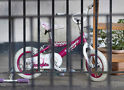 © Licensed to London News Pictures. 01/07/2020. London, UK. A child's bicycle and scooter can be seen as police guard a block of flats in Monarch Parade in Mitcham, south London after a four year old girl was found seriously injured yesterday. She was taken to hospital where she later died. A woman, aged 35, is fighting for her life after she was also found suffering serious injuries inside the property. Photo credit: Peter Macdiarmid/LNP