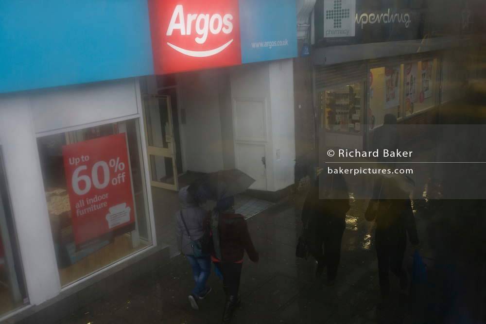 Aerial view through misted bus window of Argos branch and Londoners drab lives below during seasonal downpour of rain.