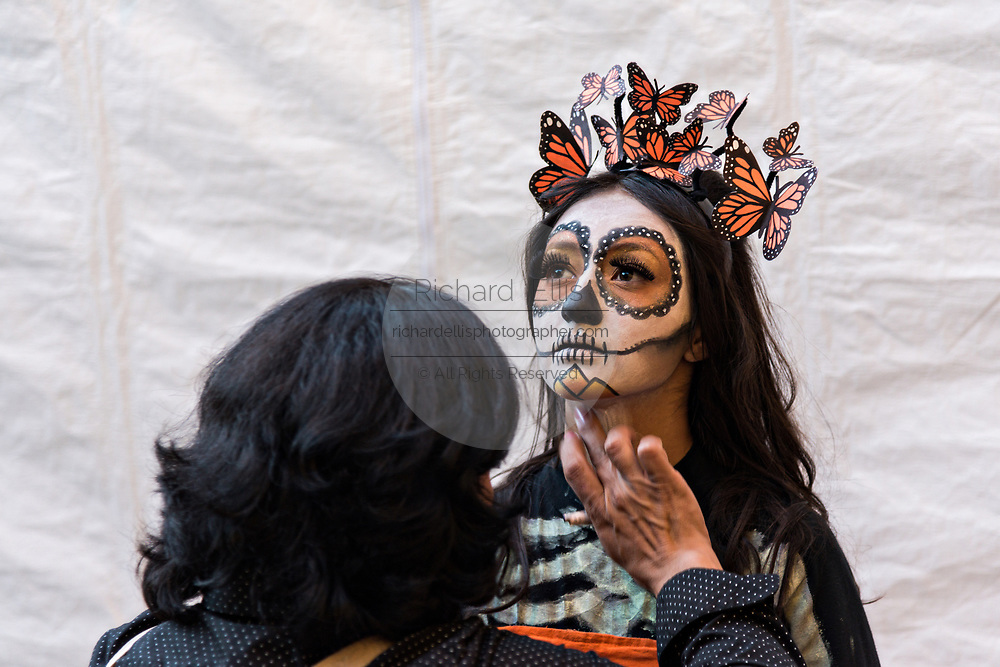 A young Mexican woman has face paint applied for her La Calavera Catrina costume during the Day of the Dead or Día de Muertos festival October 29, 2017 in San Miguel de Allende, Guanajuato, Mexico. The festival has been celebrated since the Aztec empire celebrates ancestors and deceased loved ones.