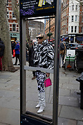 Framed in the missing panels of a map of the capital's West End theatre district, a woman fashionista wearing a monochrome outfit stands outside in the street before an event held at the National Portrait Gallery during London Fashion Week, on 17th February 2020, in London, England.
