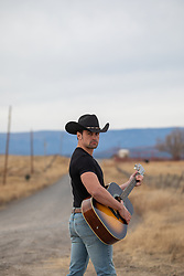 attractive cowboy holding a guitar on a rural ranch