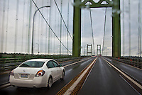 a white car crosses the older Tacoma Narrows Bridge in the rain - Tacoma, WA, USA