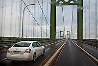 a white car crosses the older Tacoma Narrows Bridge in the rain - Tacoma, WA, USA