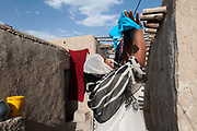 Afghanistan. Charahi Spinkali, district 5, Kabul. Amida hangs out the washing in the courtyard of her home.