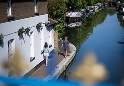 © Licensed to London News Pictures. 23/06/2020. London, UK. Members of the public make their way along the towpath of Grand Union Canal at Little Venice in central London at the beginning of a warm summers day. Record temperatures are expected this week as the UK starts to relax lockdown restrictions, introduced earlier this year to prevent the spread of COVID-19. Photo credit: Ben Cawthra/LNP