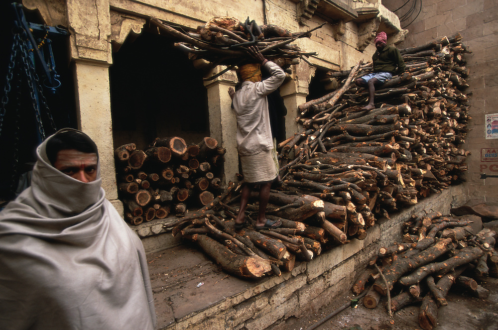 Men piling up firewood for the funeral pyres at Manikarnika Ghat, the main cremation ghat of Varanasi. India. The work at the cremation ghat is carried out by the Doms, traditionally looked upon as untouchables. To be cremated in the sacred city of Varanasi means a straight passage to heaven, many Hindus believe.