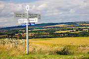 Signpost at rural crossroads in The Cotswolds gives directions for Burford and the Oxfordshire Cycleway, UK