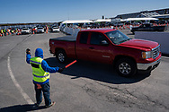 A worker directs cars as Lehigh Valley Health Network holds a COVID-19 mass vaccination clinic Mar. 20, 2021, at Pocono Raceway in Long Pond, Pennsylvania. Administrators were expected to vaccinate 3,000 people in the state of Pennsylvania's Phase 1A with the Moderna vaccine.