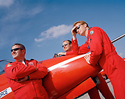 Pilots of the Red Arrows, Britain's RAF aerobatic team watch other aviators' display flying during airshow. Officer pilots of the elite 'Red Arrows', Britain's prestigious Royal Air Force aerobatic team, lean against the nose of their Hawk jet before themselves flying their own air display. Their leaning curve is steep, even for these accomplished fast-jet aviators who had already accumulated 1,500 hours in fighters. By Summer they need every aspect of their 25-minute displays honed to perfection.