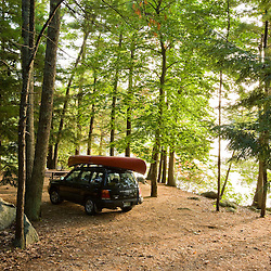 A car and a canoe at a campsite next to Pawtuckaway Lake on Horse Island in New Hampshire's Pawtuckaway State Park.