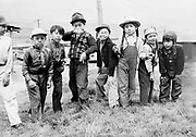 9305-B7044. Eight Indian children at Celilo Village, May 1940. (left to right) 1=?, 2= Dewey Canapoo (also spelled Canapo), 3= Nelson Billy, 4= Wallace Albert, 5=Tommy Eli, 6= Buster George, 7= Cecil Billy, 8=Russell Billy. Dewey Joe Canapoo was born September 25, 1932 and died April 11, 1952, obituary in The Dalles Chronicle, April 13, 1952, pg. 1, col. 3. He appears to be about 8 years old in this photo. Nelson Billy died November 2, 1972 at age 43 in Portland, Oregon. Story in Oregonian, November 3, 1972, pg. 35 col. 1. Buster George of Celilo returned from Army service in Korea in April 1954. Cecil Billy of Goodnoe Hills, Washington, returned from Army service in Korea in July, 1955. <br /> <br /> (Identifications by Celilo Village elders April 1994, additional identifications by contemporary Celilo resident September 2012) Horvath notch code #14B. Emulsion #33. Other photos taken about the same time, with the same emulsion number, are 9305-A4312-1, 9305-A4312-5, 9305-B7044, 9305-B7046.  B7046 was published in the Oregon Journal on May 12, 1940 and Everett Olmstead was credited as the photographer. 9305-A4312-5 shows a 1940 license plate on a Ford car.
