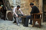 Arab shop keeprs Play backgammon in front of their shop, in the bazaar  Old City, Jerusalem, Israel