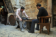 Arab shop keeprs Play backgammon in front of their shop, in the bazaar  Old City, Jerusalem, Israel
