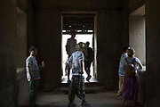 Tourists looking around and examining inside the ancient temple of Angkor Wat, Krong Siem Reap, Cambodia. Angkor Wat is a temple complex in Cambodia and the largest religious monument in the world, with the site measuring 162.6 hectares. It is Cambodia's main tourist destination.
