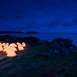 Cemaes Bay, Anglesey, UK. 20th July 2012. As part of the Cultural Olympiad, Artichoke collaborated with Fiona Shaw to produce 8 peace camps around the UK. Glowing beacons of peace speaking poetry from dusk till dawn.