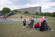 Park life in Burgess Park playground on 31st July 2015 in South London, United Kingdom. On the horizon is the Aylesbury Estate, a large housing estate located in Walworth, South East London. It contains 2,704 dwellings and was built between 1963 and 1977. The whole estate is currently undergoing a major redevelopment with most of the dwellings are derelict.