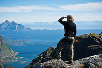 Hiker enjoys view from summit of Justadtind, Lofoten islands, Norway